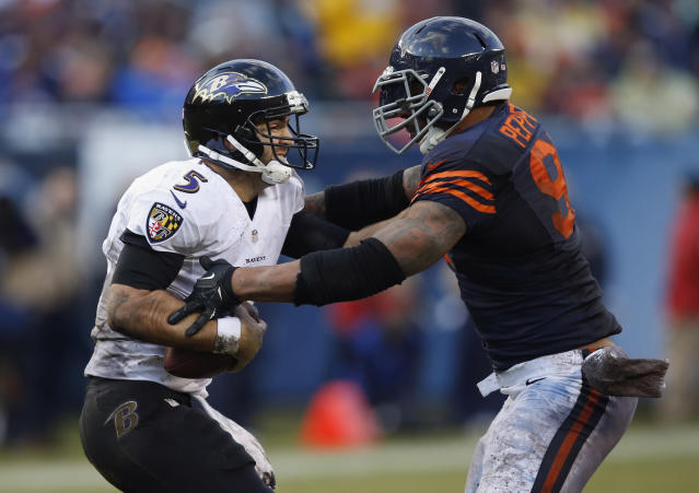 Baltimore Ravens quarterback Joe Flacco (5) pushes off Chicago Bears defensive end Julius Peppers (90) during the first half of an NFL football game, Sunday, Nov. 17, 2013, in Chicago. (AP Photo/Charles Rex Arbogast)
