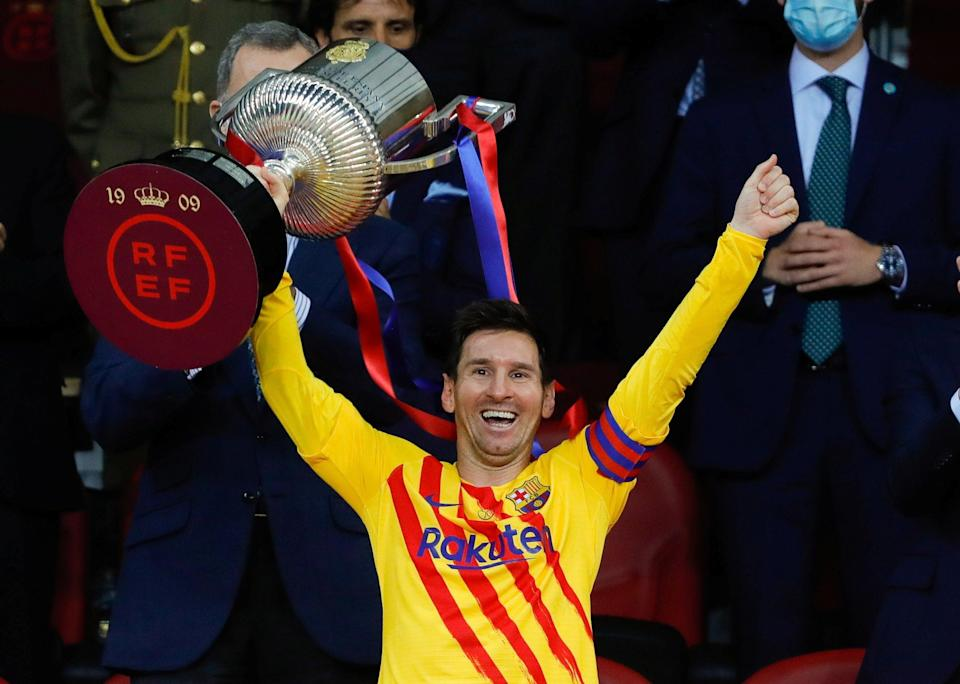 Lionel Messi celebrates with the trophy (Reuters)
