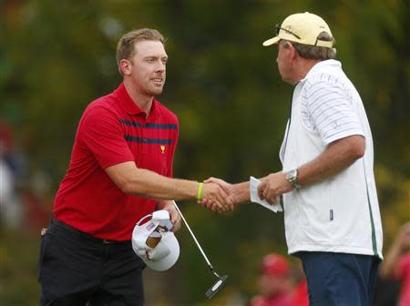 Mahan of the U.S. shakes hands with International team captain Price of Zimbabwe at the 2013 Presidents Cup golf tournament at Muirfield Village Golf Club in Dublin, Ohio