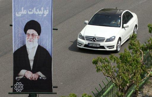 An Iranian man drives a Mercedes past a portrait of Iran's supreme leader, Ayatollah Ali Khamenei in northern Tehran on Sunday. Wealthy Iranians are fuelling an unprecedented luxury car boom despite sanctions hurting their economy, paying up to $360,000 for high-end autos, according to showroom employees and reports on Sunday