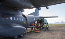 "This photo provided by the French Defense Ministry shows a French military transport aircraft carrying pollution control equipment after landing in Mauritius island, Sunday Aug.9, 2020. The Indian Ocean island of Mauritius has declared a ""state of environmental emergency"" after the Japanese-owned ship that ran aground offshore days ago began spilling tons of fuel. (Gwendoline Defente/EMAE via AP)"