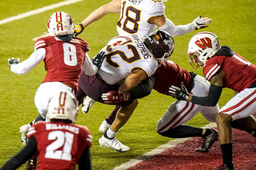 Minnesota wide receiver Mike Brown-Stephens (22) scores a touchdown against Wisconsin cornerback Deron Harrell (8), safety Scott Nelson, behind, and cornerback Faion Hicks (1) during the second half of an NCAA college football game Saturday, Dec. 19, 2020, in Madison, Wis. (AP Photo/Andy Manis)