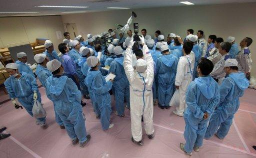 This file photo shows members of the media, wearing protective suits, interviewing Japan's Minister of the Environment Goshi Hosono and then Chief of the Dai-ichi nuclear plant Masao Yoshida, inside the emergency operation center at the crippled plant, in 2011