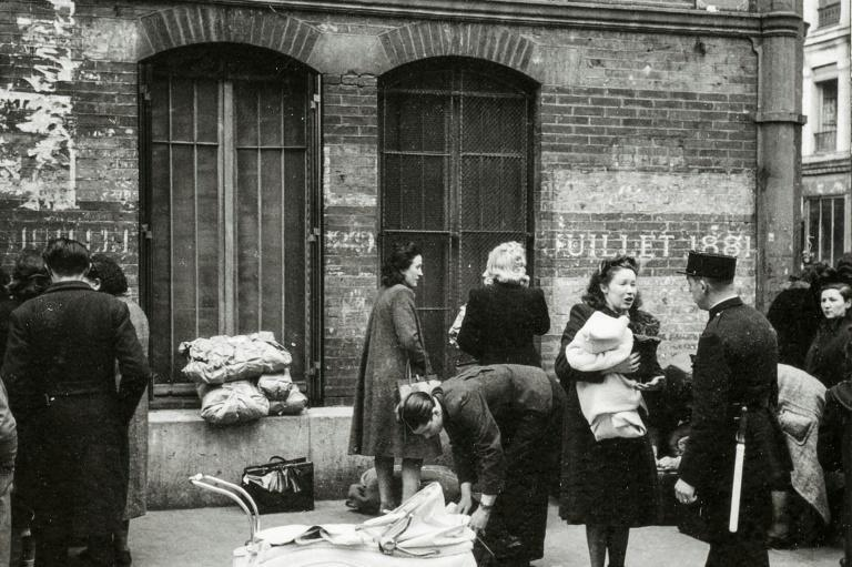 This photo from May 14, 1941 shows the wives of foreigners of Jewish faith in Paris speaking with a police officer in front of the Japy gymnasium