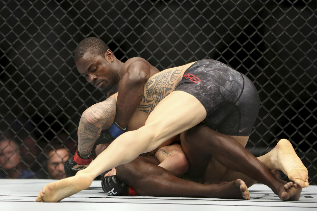 Abdul Razak Alhassan, top, grapples Sabah Homasi during a mixed martial arts bout at UFC 220, Saturday, Jan. 20, 2018, in Boston. Alhassan won via 1st round knockout. (AP Photo/Gregory Payan)