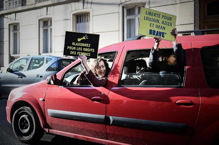 """Women hold signs reading """"honk for women's rights"""" and """"freedom for Loujain, Aziza and Iman"""" during a protest organised by Amnesty International outside the Saudi Arabia embassy in Paris, on March 8, 2019 to mark International Women's Day (AFP Photo/Philippe LOPEZ)"""