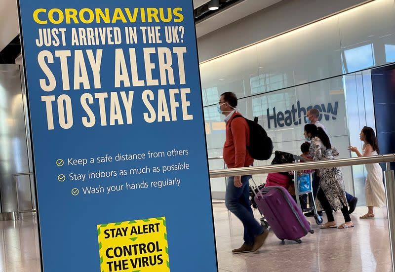 A public health campaign message is seen as passengers from international flights arrive at Heathrow Airport, following the outbreak of the coronavirus disease (COVID-19), London, Britain