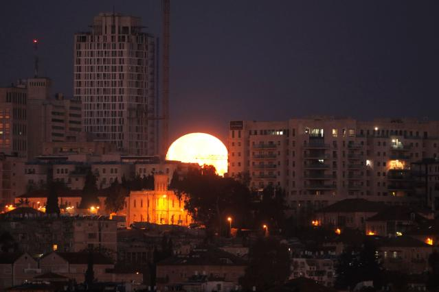 <p>The moon sets behind the city of Jerusalem early on Jan. 31, 2018. (Photo: Menahem Kahana/AFP/Getty Images) </p>