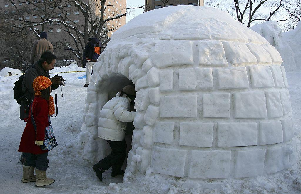 SAPPORO, JAPAN - FEBRUARY 12: Children enter an igloo during the 57th Sapporo Snow Festival February 12, 2006 in Sapporo, Hokkaido, Japan. Two million people are expected to visit the annual week long festival featuring snow and ice scupltures from around the world, it is the largest winter attraction in Hokkaido. (Photo by Cameron Spencer/Getty Images)