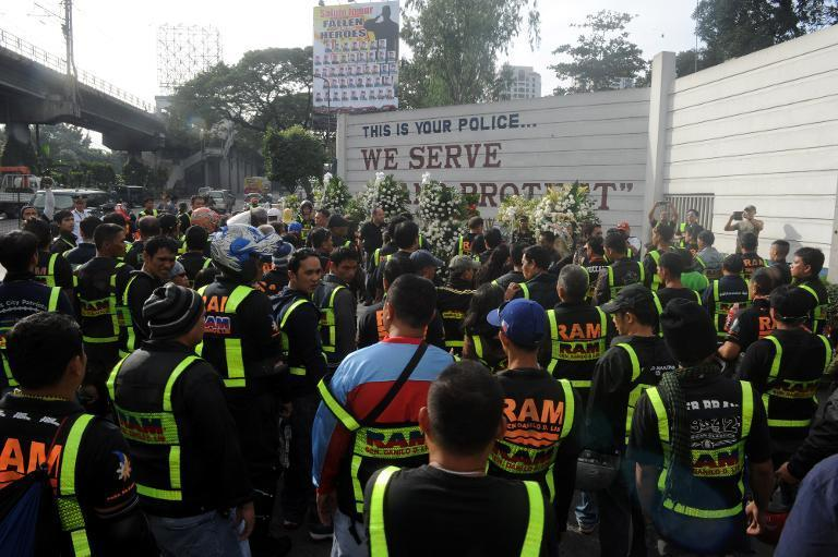 Mourners gather at the gates of the National Police headquarters in Manila, on February 1, 2015, to pay respects to 44 elite police commandos who died in Mamasapano town on the strife-torn southern island of Mindanao