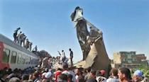 Twisted metal juts out from the wreckage of a train collision that killed at least 32 people and injured 91 in southern Egypt