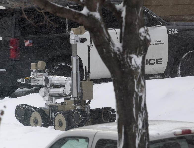 "A robot is used as authorities respond to the scene of a shooting on Oakland Avenue South, Sunday, Dec. 1, 2019, in Minneapolis. Two boys were found shot late Sunday morning outside the residence, where two adults were found dead later in the day. The two boys were also later pronounced dead, in what police are calling a ""domestic related incident."" (Kevin Martin/Star Tribune via AP)"