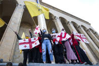 Supporters of the ex-President Mikhail Saakashvili's United National Movement, most of them wearing face masks to help curb the spread of the coronavirus, wave Georgian national and movement flags during rally to protest the election results, in front of the parliament's building in Tbilisi, Georgia, Sunday, Nov. 1, 2020. Preliminary election results show that Georgia's ruling party won the country's highly contested parliamentary election, but the opposition have refused to recognize Sunday's results. (AP Photo/Shakh Aivazov)