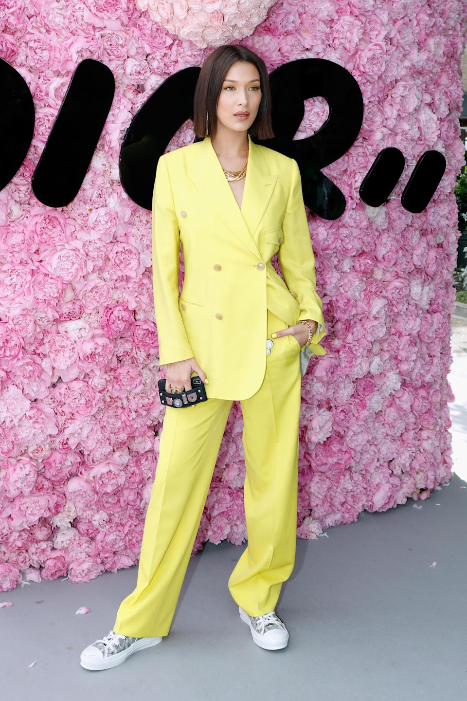 <p>Bella Hadid went striking in yellow at the Dior Homme show for Paris Fashion Week, co-ordinating her neon look right down to her eyeshadow and nail varnish. <br><em>[Photo: Getty]</em> </p>