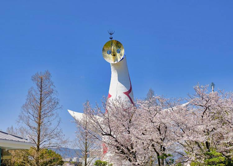 Tower of the Sun, designed with three faces on the outside and a fourth inside, and cherry blossoms