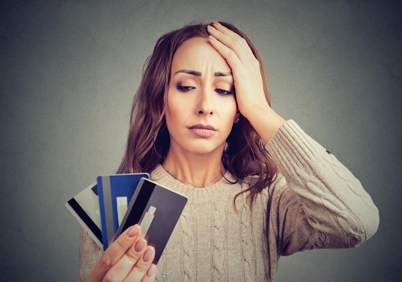 Woman looking at three credit cards with frustrated face