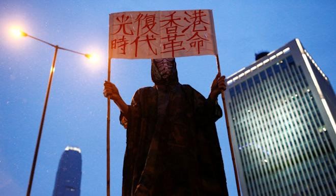 """An anti-extradition bill protester holds a placard that reads """"Liberate Hong Kong; revolution of our times"""" outside the People's Liberation Army headquarters in Hong Kong. Photo: Thomas Peter"""