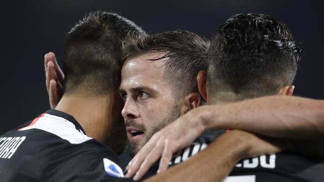 Juventus' Miralem Pjanic celebrates with his teammates Cristiano Ronaldo, right, and Juventus' Sami Khedira after scoring his side's second goal during a Serie A soccer match between Juventus and Bologna, at the Allianz stadium in Turin, Italy, Saturday, Oct.19, 2019. (AP Photo/Luca Bruno)