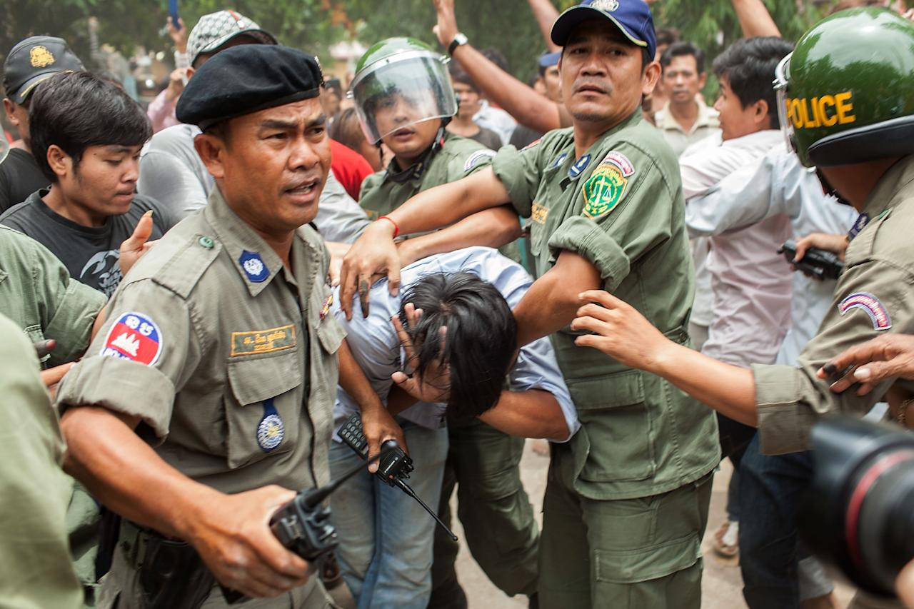 PHNOM PENH, CAMBODIA - JULY 28: Police escort a man during a mob attacked in front of a polling station, the man had been accused of striking a monk during an altercation between voters and the National Election Committee employee in charge of the polling station, (the National Election Committee staff member was accused of denying people the right to vote) during the Cambodian general elections on July 28, 2013 in Phnom Penh, Cambodia Cambodians go to the polls today in the fifth parliamentary election since 1993. 123 seats in the National Assembly are up for grabs to eight listed parties, with the main contenders being the ruling Cambodian Peoples Party (CPP) and the leading opposition Cambodia National Rescue Party (CNRP) led by Sam Rainsy. (Photo by Nicolas Axelrod/Getty Images)