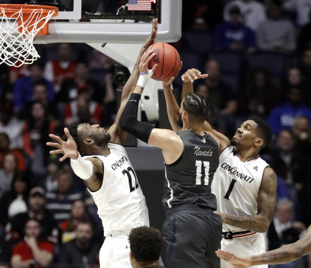 Nevada forward Cody Martin (11) drives to the basket as Cincinnati guard Jacob Evans (1) and forward Eliel Nsoseme (22) defend, during the first half of a second-round game in the NCAA college basketball tournament in Nashville, Tenn., Sunday, March 18, 2018. (AP Photo/Mark Humphrey)