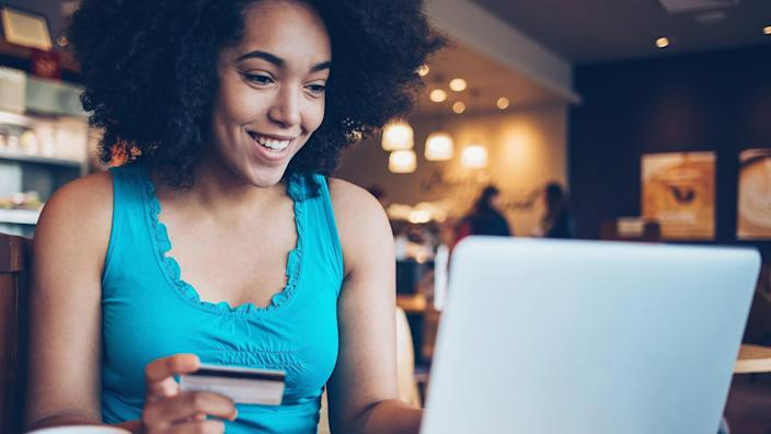 Smiling young African ethnicity woman sitting in cafe, holding a credit card and typing on a laptop.