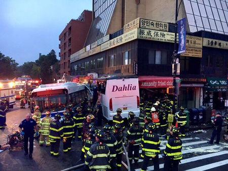 A New York City transit bus and a tour bus collided spinning around before slamming into a building in Queens