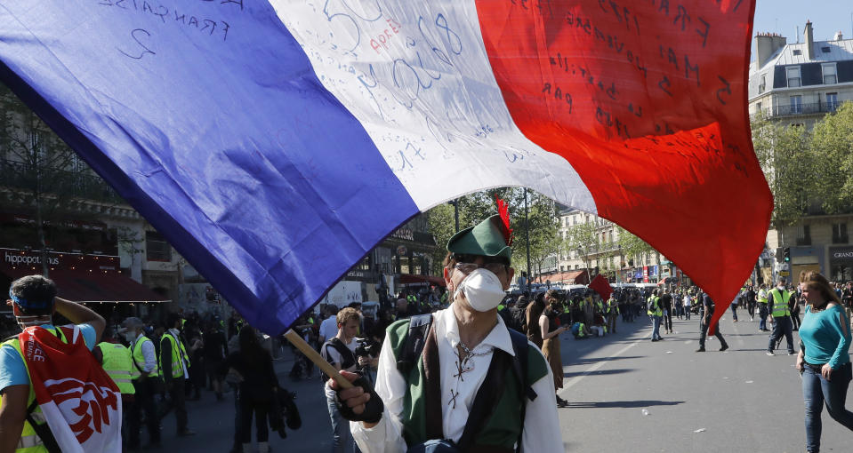 A man dressed as Robinhood waves the French flag during a yellow vest demonstration in Paris, Saturday, April 20, 2019. French yellow vest protesters are marching anew to remind the government that rebuilding the fire-ravaged Notre Dame Cathedral isn't the only problem the nation needs to solve. (AP Photo/Michel Euler)
