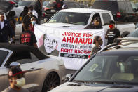 """Estevan Hernandez and Claudia Andrade hold a """"Justice for Ahmaud"""" sign at a rally in Atlanta before driving down to Brunswick, Ga., Saturday, May 16, 2020. (Steve Schaefer/Atlanta Journal-Constitution via AP)"""