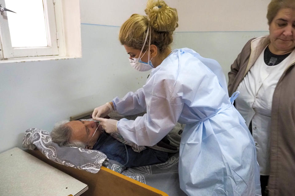 A nurse cares for a coronavirus patient in an infectious diseases clinic in Stepanakert, the separatist region of Nagorno-Karabakh, Tuesday, Oct. 20, 2020. Nagorno-Karabakh, which lies within Azerbaijan but has been under the control of ethnic Armenian forces since a war there ended in 1994, faces an outbreak of the coronavirus amid the largest outbreak of hostilities in more than a quarter-century. (AP Photo)