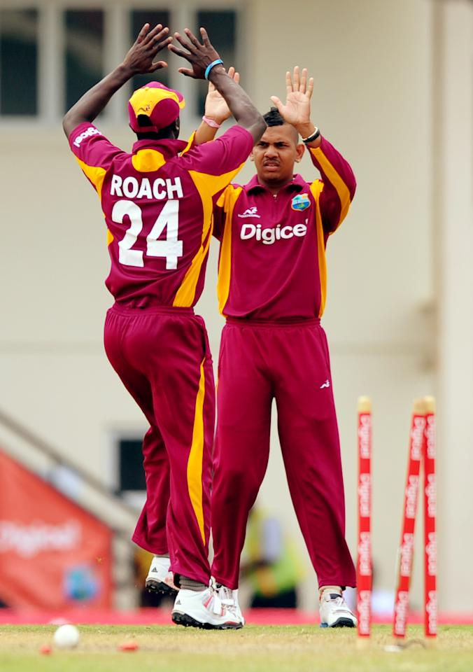 West Indies cricketers Kemar Roach (L) and Sunil Narine (R) celebrate after dismissing Australian batsman Brett Lee during the fifth-of-five One Day International (ODI) matches between West Indies and Australia at the Beausejour Cricket Ground in Gros Islet, St. Lucia on March 25, 2012.     AFP PHOTO/Jim Watson (Photo credit should read JIM WATSON/AFP/Getty Images)