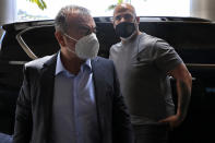 Fugitive ex-auto magnate Carlos Ghosn, foreground, steps out from a Nissan SUV, as he escorted by his bodyguard, as he arrived for an interview with The Associated Press, in Dbayeh, north of Beirut, Lebanon, Tuesday, May 25, 2021. The embattled former chairman of the Renault-Nissan-Mitsubishi alliance dissected his legal troubles in Japan, France and the Netherlands, detailed how he plotted his brazen escape from Osaka, and reflected on his new reality in crisis-hit Lebanon, where he is stuck for the foreseeable future. (AP Photo/Hussein Malla)