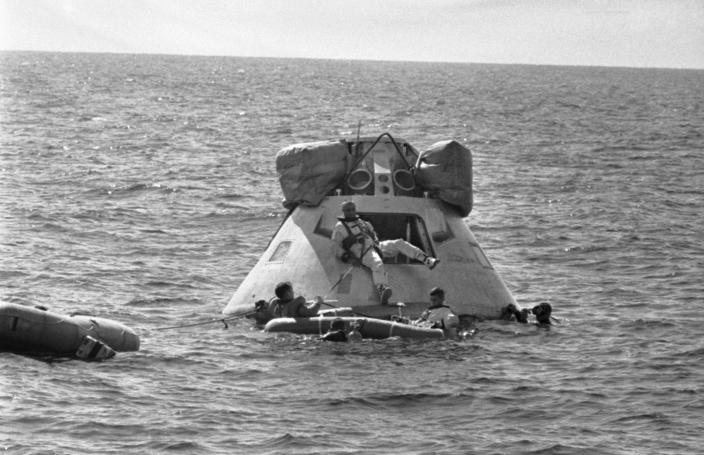 FILE - In this Oct. 27, 1966 file photo, astronaut Virgil Grissom, center, prepares to join his crew aboard a rubber raft as he leaves an Apollo spacecraft in the Gulf of Mexico during training about five miles off the coast of Galveston, Texas. Edward H. White II is at left in the raft and Roger B. Chaffee, is at right. (AP Photo/Ed Kolenovsky)
