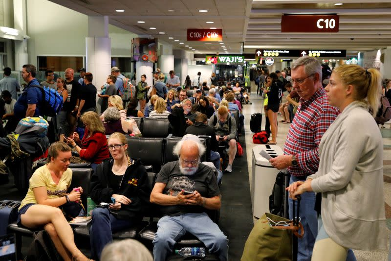 FILE PHOTO: Air Alaska passengers wait in the terminal following an incident where an airline employee took off in an airplane, at Seattle-Tacoma International Airport in Seattle, Washington