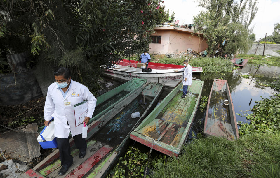 Dr. Jorge Ballesteros gets off a boat on his way to collect samples to test for COVID-19 at a home, in Xochimilco, Mexico City, Wednesday, August 5, 2020. (AP Photo/Eduardo Verdugo)