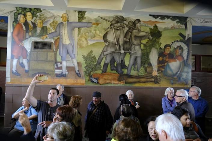 """FILE - In this Aug. 1, 2019, file photo, people fill the main entryway of George Washington High School to view the controversial 13-panel, 1,600-square foot mural, the """"Life of Washington,"""" during an open house for the public in San Francisco. San Francisco Unified School District Board of Education President Stevon Cook says he plans to introduce a solution at the school board meeting Tuesday, August 13, 2019 to cover the """"Life of Washington"""" mural without destroying it.. (AP Photo/Eric Risberg, File)"""