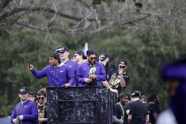 LSU players toss beads and ride on floats during a parade celebrating their NCAA college football championship, Saturday, Jan. 18, 2020, on the LSU campus in Baton Rouge, La. (AP Photo/Gerald Herbert)