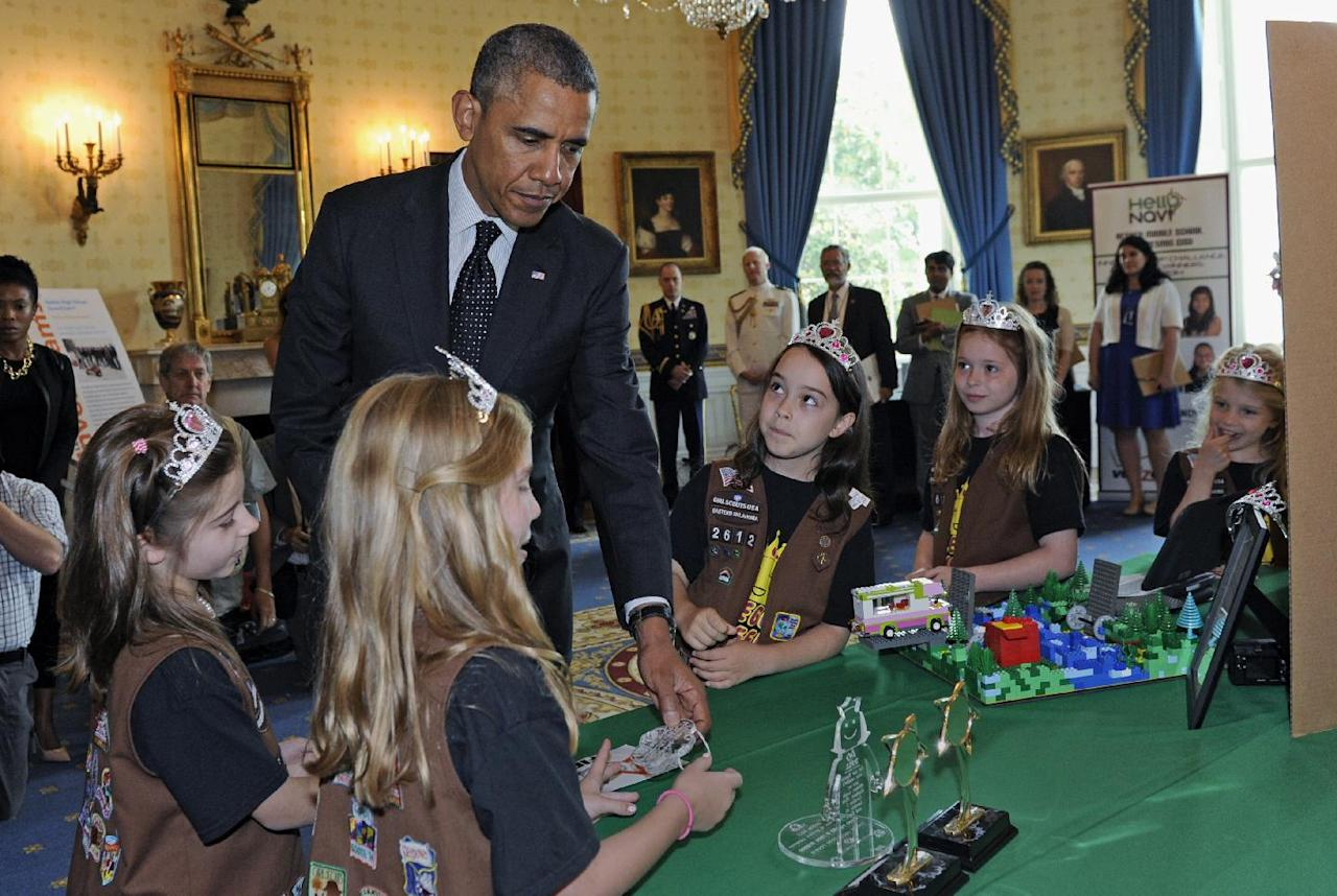 "President Barack Obama looks over the ""flood-proof"" bridge design by a group of girl scouts from Tulsa, Okla., as he tours the 2014 White House Science Fair exhibits that are on display in the State Dining Room of the White House in Washington, Tuesday, May 27, 2014. Obama was celebrating the student winners of a broad range of science, technology, engineering and math (STEM) competitions from across the country. (AP Photo/Susan Walsh)"