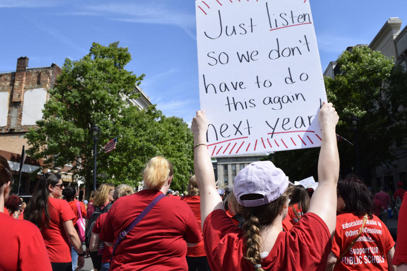As she approached the North Carolina legislative office in Raleigh, N.C., Allison Carey, 23, a third grade teacher at Powell Elementary School in Raleigh, hoists her sign up high, Wednesday, May 1, 2019. North Carolina teachers took to the streets Wednesday for the second year in a row with hopes that a more politically balanced legislature will be more willing to meet their demands. (AP Photo/Amanda Morris)