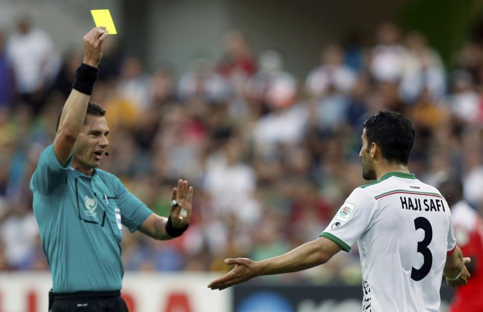 Referee Benjamin Williams of Australia shows the yellow card to Iran's Ehsan Hajisafi during the Asian Cup Group C soccer match against Bahrain at the Rectangular stadium in Melbourne January 11, 2015. REUTERS/Brandon Malone (AUSTRALIA - Tags: SOCCER SPORT)