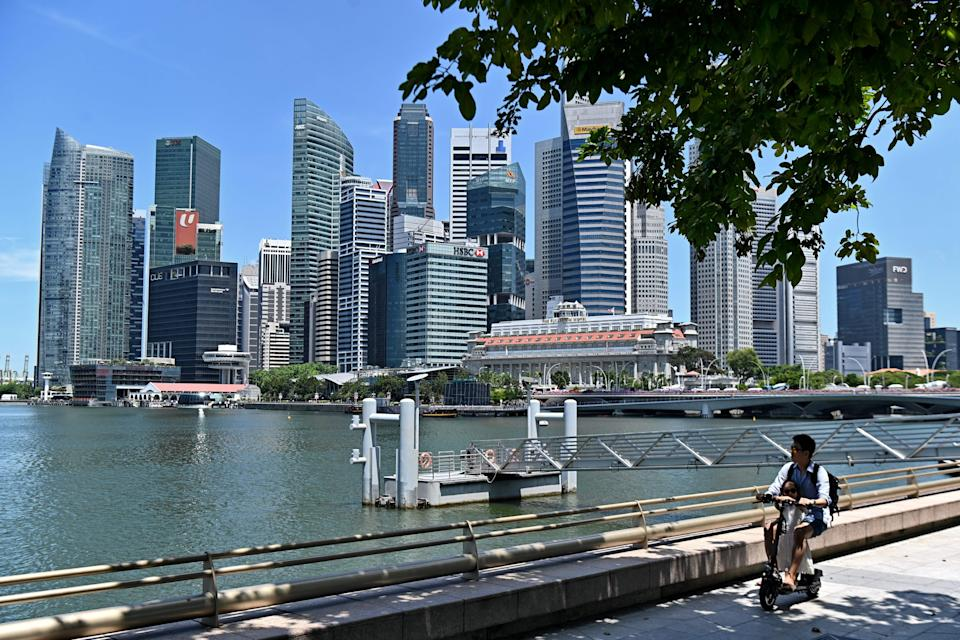 This photograph taken on May 6, 2019, shows a man and a child riding an electric scooter near the central business district in Singapore. (Photo by Roslan RAHMAN / AFP)        (Photo credit should read ROSLAN RAHMAN/AFP via Getty Images)