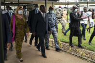 Ivory Coast President Alassane Ouattara, center, and his wife Dominique Ouattara, left, leave after voting in a polling station during presidential elections in Abidjan, Ivory Coast, Saturday, Oct. 31, 2020. Tens of thousands of security forces deployed across Ivory Coast on Saturday as the leading opposition parties boycotted the election, calling President Ouattara's bid for a third term illegal. (AP Photo/Leo Correa)