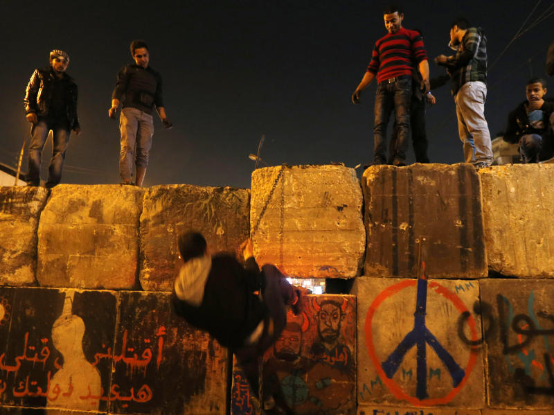 "Protesters dismantle a wall guarding the presidential palace during a demonstration in Cairo, Egypt, Tuesday, Dec. 11, 2012. Arabic writing reads, ""killing me won't bring back your regime."" Thousands of opponents and supporters of Egypt's Islamist president staged rival rallies in the nation's capital Tuesday, four days ahead a nationwide referendum on a contentious draft constitution. (AP Photo/Petr David Josek)"