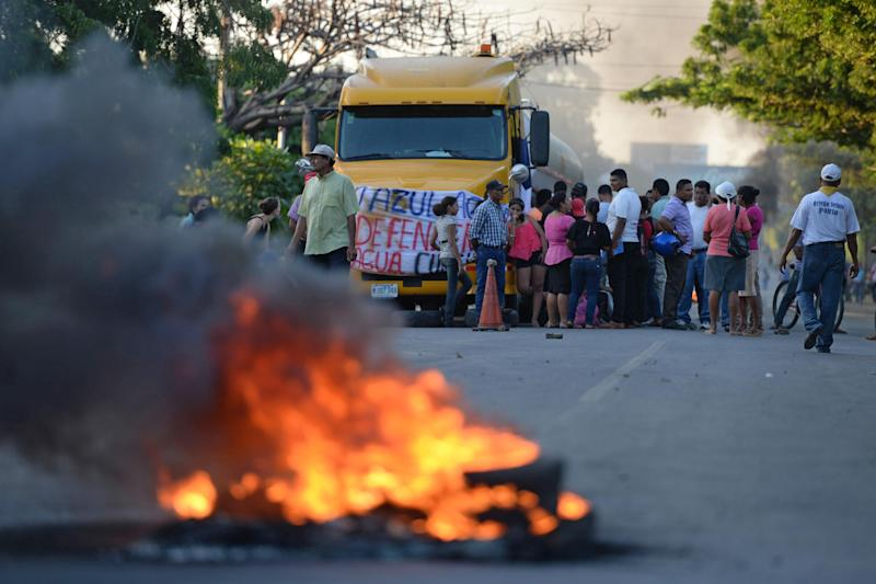 People protest burning tires against the inauguration of the works of an inter-oceanic canal in Rivas, Nicaragua on December 22, 2014