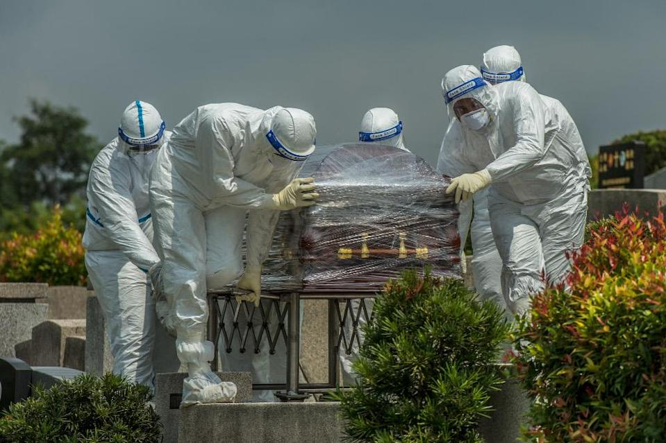 Workers in PPE suits carry the body of a person who died from the coronavirus disease (Covid-19) at a Christian cemetery in Semenyih, Selangor. — Picture by Shafwan Zaidon