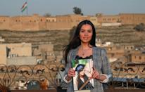 In Iraqi Kurdistan, Dima al-Kaed, 29, clutches a memento of her graduation, one of the few belongings she kept after her family moved from Damascus