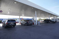 """A Department of Public Safety vehicle, right, leaves a gas station while two others are parked at pumps, Wednesday, Sept. 22, 2021, in Del Rio, Texas. The """"amistad,"""" or friendship, that Del Rio, Texas, and Ciudad Acuña, Mexico, celebrate with a festival each year has been important in helping them deal with the challenges from a migrant camp that shut down the border bridge between the two communities for more than a week. Federal officials announced the border crossing would reopen to passenger traffic late Saturday afternoon and to cargo traffic on Monday. (AP Photo/Julio Cortez)"""