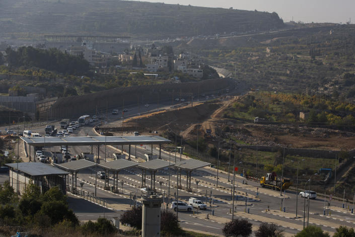 """FILE - In this Sunday, Nov. 29, 2020. file photo, roadworks expand a road to Israeli settlements inside the West Bank, near the city of Bethlehem. Israel's premier human rights group has begun describing both Israel and its control of the Palestinian territories as a single """"apartheid"""" regime, using an explosive term that the Israeli government and its supporters vehemently reject. (AP Photo/Majdi Mohammed, File)"""