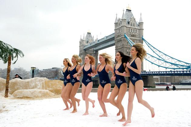 "Models in swimwear run together through the snow at a ""pop-up beach resort"" promotion in front of Tower Bridge in central London on January 21, 2013. Britain is braced for a continuation of the bad weather which has schools closed and caused transport chaos in recent days, with several weather warnings in place. AFP PHOTO / CARL COURT"