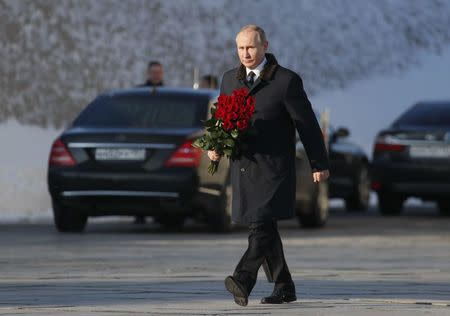 Russian President Putin attends a wreath laying ceremony at the eternal flame during an event to commemorate the 75th anniversary of the battle of Stalingrad in World War Two, at the Mamayev Kurgan memorial complex in Volgograd