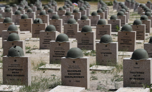 In this photo taken on Sunday, June 17, 2018, graves of Russian soldiers in a cemetery near Stalingrad in Rossoshka, Russia, . 72-year-old Vitaly Danilkin takes care of a cemetery some 40 miles northwest of Volgograd in Rossoshka, for German soldiers who perished at Stalingrad and nearby Rostov-on-Don, as well as a Soviet cemetery on the other side of the road. Nearly 60 years since it changed its name to Volgograd, the Russian city once called Stalingrad and its bloody history loom large even in the midst of the fun and football of the World Cup. (AP Photo/Frank Augstein)